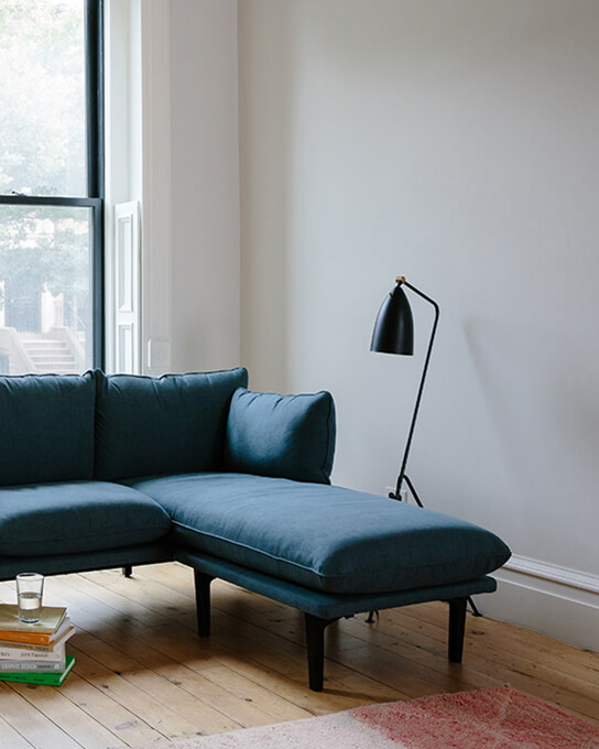 The Three-Seater Floyd Sofa plus Chaise in Ocean Dive with an Upholstered base displayed in a living room
